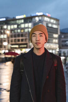 Portrait of stylish man with yellow hat in the city at night - AHSF02287