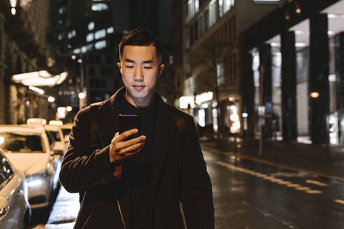 Man using smartphone while walking in the city at night - AHSF02296