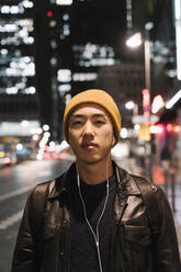 Portrait of stylish man with yellow hat and earphones in the city at night - AHSF02302