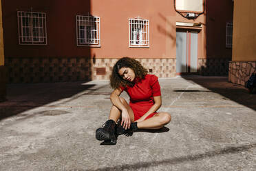 Young woman wearing red dress and sitting on ground - TCEF00499