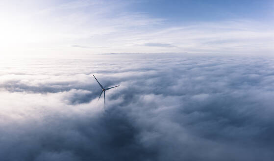 Germany, Aerial view of wind turbine shrouded in clouds at dawn - WFF00328