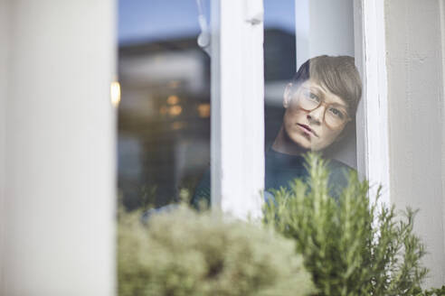 Pensive woman at home looking out of window - MCF00659