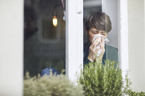 Woman blowing her nose at home at the window - MCF00662