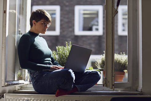 Woman sitting at the window at home using laptop - MCF00668