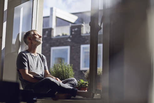 Mature man sitting at the window at home with closed eyes - MCF00671