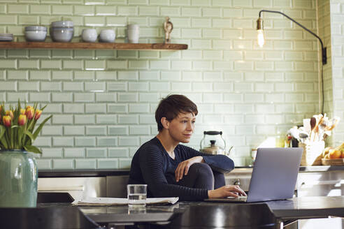 Woman sitting at tkitchen table at home using laptop - MCF00704