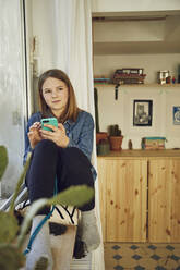 Girl sitting at the window at home holding smartphone - MCF00710