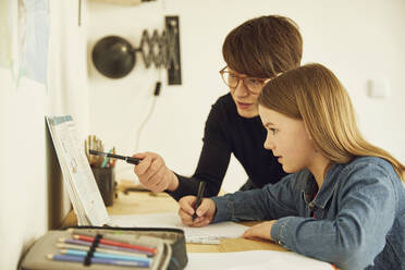 Mother helping daughter doing homework at home - MCF00713