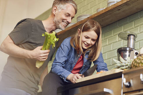 Happy father and daughter in kitchen preparing vegetables - MCF00716