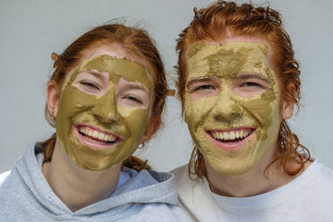 Portrait of laughing brother and sister with facial masks - LBF03045