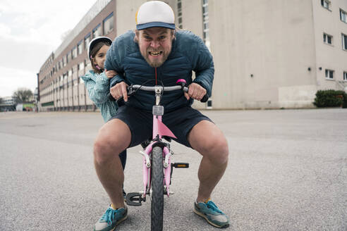 Playful father with daughter on her bicycle - JOSEF00290