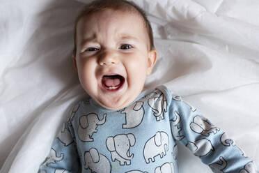 Baby girl teething, lying on bed - GEMF03600