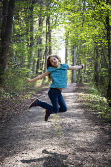 Portrait of girl jumping in the air on forest track - LVF08836
