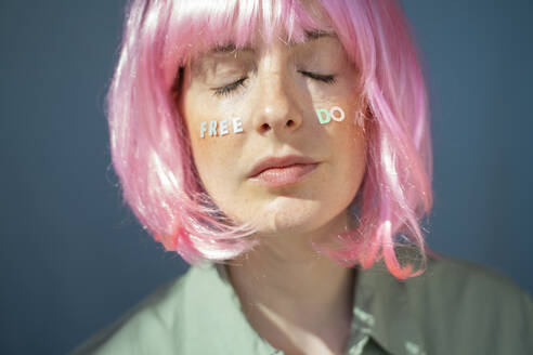 Young woman wearing pink wig, letters on her face, freedom - AFVF06105