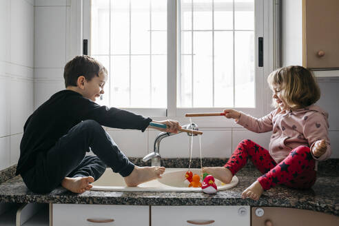Boy and his little sister fishing rubber ducks in kitchen sink - JRFF04350