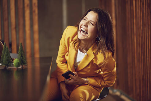 Laughing businesswoman wearing yellow suit sitting at desk in office - MCF00733