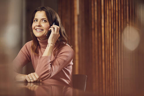 Smiling businesswoman on the phone sitting at desk in office - MCF00757