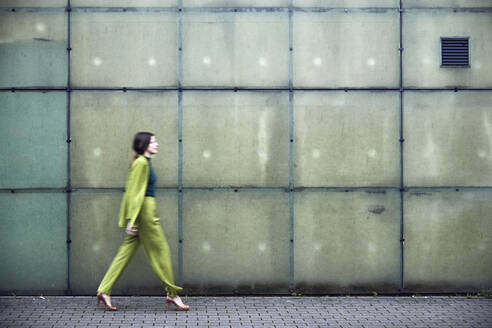 Businesswoman wearing green suit passing a wall - MCF00772
