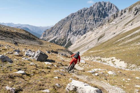 Man riding on mountainbike, Munestertal Valley, Grisons, Switzerland - HBIF00105