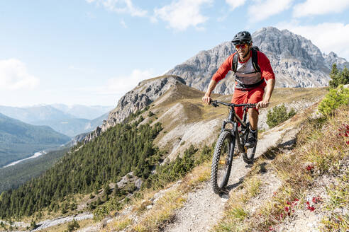 Man riding on mountainbike, Munestertal Valley, Grisons, Switzerland - HBIF00111