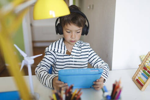 Boy doing homeschooling and using tablet and headphones at home - HMEF00894