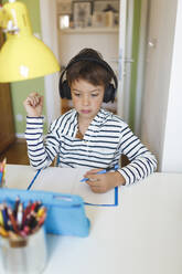 Boy doing homeschooling and writing on notebook, using tablet and headphones at home - HMEF00900