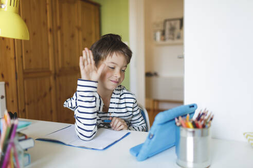 Boy doing homeschooling and using tablet at home - HMEF00909