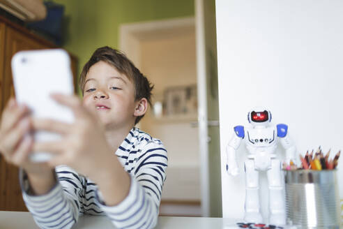 Boy doing homeschooling and using smartphone at home - HMEF00912