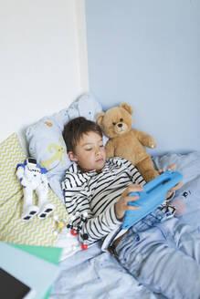 Boy lying in bed using digital tablet - HMEF00915