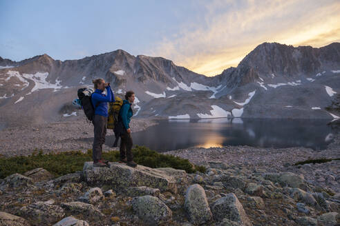Women hikers watch sunset from Pierre Lakes, Elk Mountains, Colorado - CAVF79082