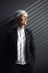 Portrait of fashionable senior businesswoman in front of grey wall looking at distance - RBF07601