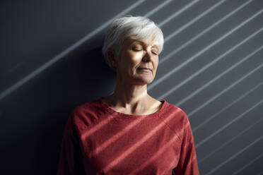 Portrait of senior woman with eyes closed leaning against wall - RBF07604
