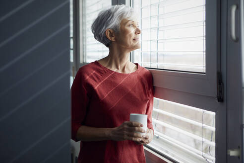 Portrait of senior woman with coffee mug looking out of window - RBF07607