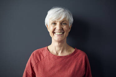 Portrait of happy senior woman wearing red shirt in front of grey wall - RBF07610