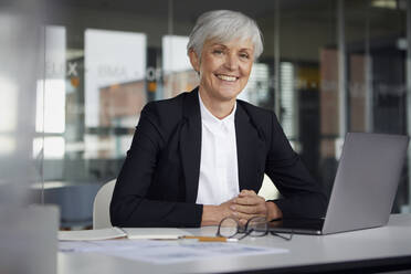 Portrait of smiling senior businesswoman sitting at desk in office - RBF07613