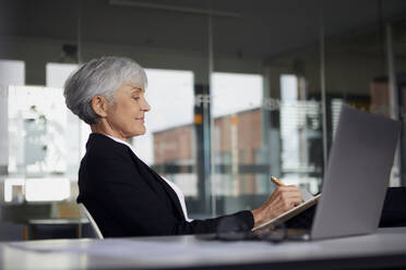 Senior businesswoman sitting at desk writing in notebook - RBF07616
