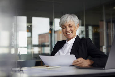 Portrait of smiling senior businesswoman sitting at desk looking at documents - RBF07619