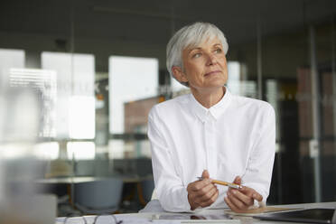 Portrait of pensive senior businesswoman at desk in her office - RBF07622