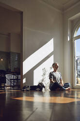 Mature man sitting on the floor at home meditating - MCF00777