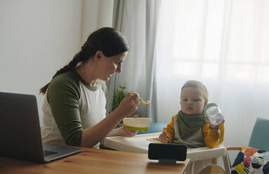 Mother feeding baby boy at home - BZF00545
