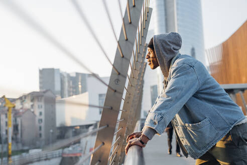 Portrait of young man standing on a bridge in the city at sunset, Milan, Italy - MEUF00467