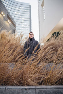 Portrait of young woman among grasses in the city - MEUF00491