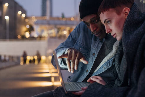 Happy young couple using laptop in the city at dusk - MEUF00500