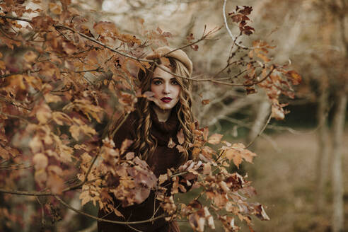 Portrait of fashionable woman standing behind autumn leaves - GMLF00084