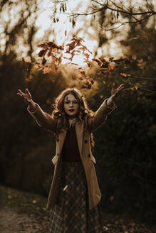 Portrait of fashionable woman throwing autumn leaves into the air - GMLF00090