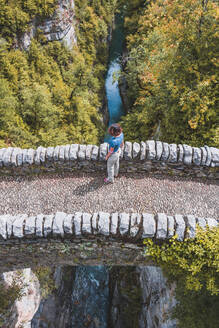 Spain, Province of Huesca, Aerial view of young woman standing on stone bridge - FVSF00200