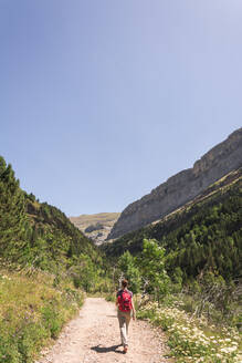Spain, Province of Huesca, Clear sky over female backpacker hiking along mountain dirt road - FVSF00215