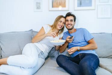 Smiling couple watching TV while enjoying popcorn on sofa at home - KIJF02980