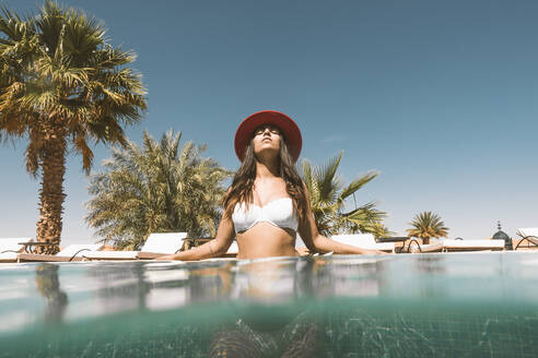 Portrait of young woman relaxing in swimming pool, Morocco - DAMF00406