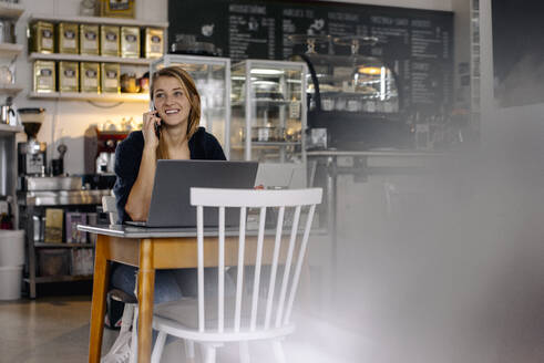 Smiling young woman using smartphone and laptop in a cafe - GUSF03513